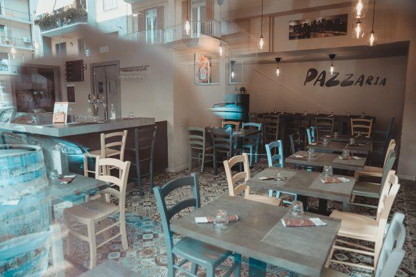 sala pizzeria con tavoli e sedie in legno